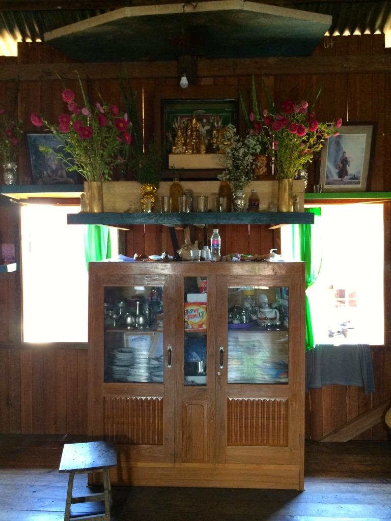 Domácí oltář plný květin a darů pro Budhu