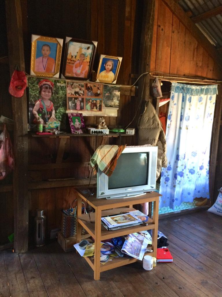 Televize s nezbytnou dekorací na stěně - fotky rodiných příslušníků.